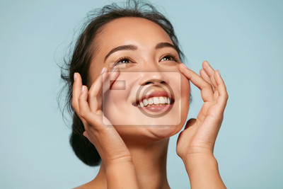 Posters Skin care. Woman with beauty face touching healthy facial skin portrait. Beautiful smiling asian girl model with natural makeup touching glowing hydrated skin on blue background closeup