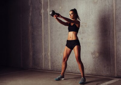 Posters Slim attrayante sportive dans une formation kettlebell