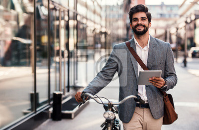 Posters Smiling businessman using tablet on the way to office. Business, education, lifestyle concept
