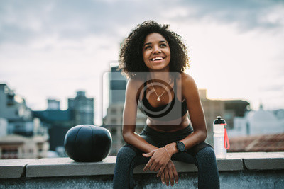 Posters Smiling woman athlete taking a break during workout