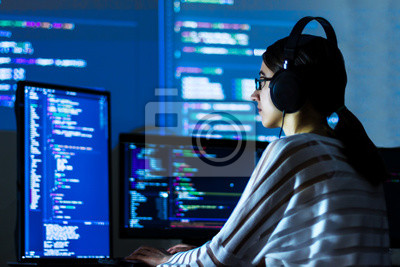 Posters Software developer freelancer woman female in glasses work with program code C++ Java Javascript on wide displays at night Develops new web desktop mobile application or framework Projector background