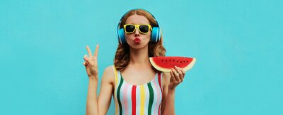 Posters Summer fashion portrait of young woman in headphones listening to music with juicy slice of watermelon, female model blowing her lips posing on a colorful blue background