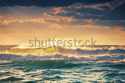 Posters Sunrise and shining waves in ocean