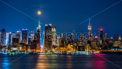 Posters Super Moon above New York skyline. The top of the Empire State Building is illuminated with the colors of the German and Argentinian flags in honor of the Soccer World Cup final.