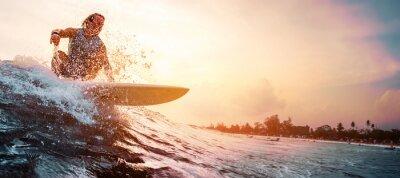 Posters Surfer surfe la vague de l'océan pendant le coucher du soleil. Sport extrême et concept de mode de vie actif