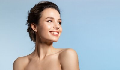 Posters Toothy smiling young woman with shiny glowing perfect facial skin and bare shoulder looking aside.