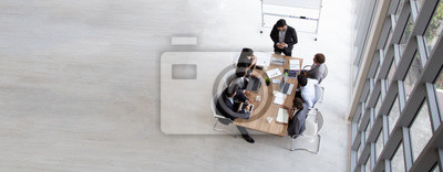 Posters Top view of group of multiethnic busy people working in an office, Aerial view with businessman and businesswoman sitting around a conference table with blank copy space, Business meeting concept