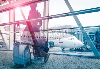 Posters Travel concept with woman and suitcase moving fast to airport terminal gate - Double exposure look with focus on the aircraft in the background - Violet marsala sun flare with vintage filtered editing