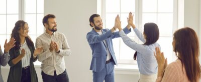 Posters Two happy cheerful business people give each other a high five while colleagues are applauding. Team of people meeting in a modern office. Group of business partners making a deal. Teamwork concept