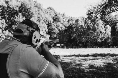 Posters Un casque uniforme de tireur d'élite sportif tire une cible de fusil de chasse