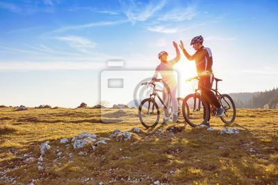 Posters Un couple heureux va sur une route asphaltée de montagne dans les bois sur des vélos avec des casques en se donnant un haut cinq