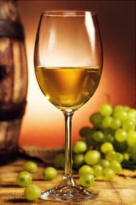 Posters Un verre de vin blanc à l'avant de raisins verts et vieux baril