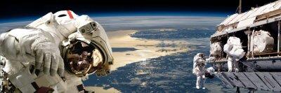 Posters Une équipe d'astronautes effectuant des travaux sur une station spatiale. - Eléments de cette image fournis par la NASA.