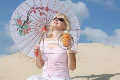 une femme avec du jus s'assied sur le sable
