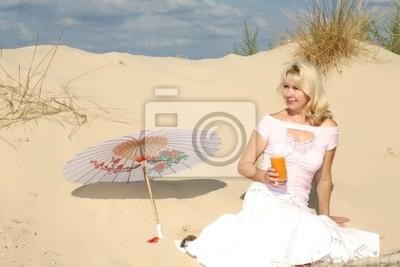une femme est assise sur le sable avec un parasol