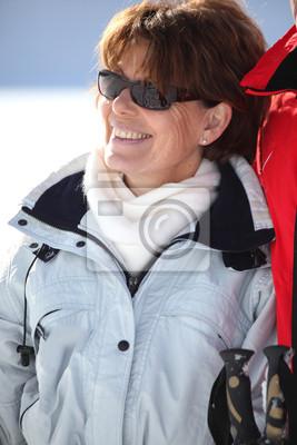 une femme mûre sourire dans une station de sports d'hiver