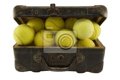 Vieille valise brune pleine de balles de tennis isolé sur fond blanc.