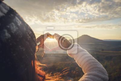Posters Voyageur de la jeune femme en forme de coeur symbole au lever du soleil