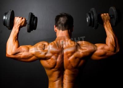 Posters vue arrière de la formation de bodybuilder avec des haltères sur fond noir