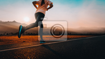 Posters Woman enjoys running outside with beautiful summer evening in the countryside.