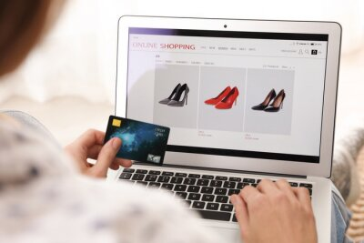 Posters Woman with credit card using laptop for online shopping indoors, closeup