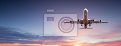 Posters Avion de ligne commercial volant au-dessus de nuages dramatiques.