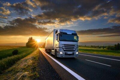 Posters Camion roulant sur la route d'asphalte dans un paysage rural au coucher du soleil avec des nuages sombres