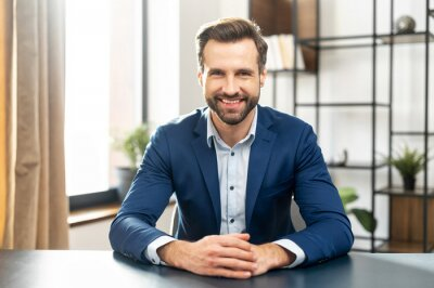 Posters Young bearded confident successful man in business casual clothes looking at camera, skilled job applicant is ready for an online interview on a video call, sitting at the desk, holding hands together