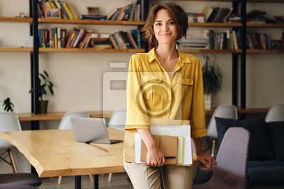 Posters Young beautiful woman in yellow shirt leaning on desk with notepad and papers in hand while happily looking in camera in modern office