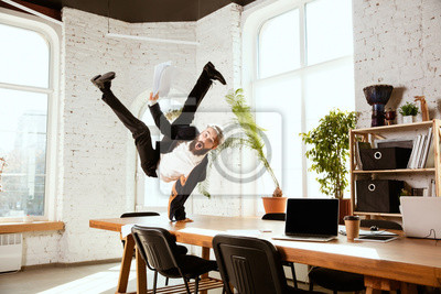 Posters Young caucasian businessman having fun dancing break dance in the modern office at work time with gadgets. Management, freedom, professional occupation, alternative way of working. Loves his job.