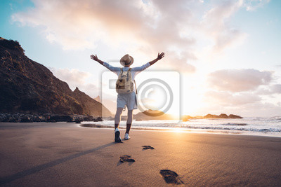 Posters Young man arms outstretched by the sea at sunrise enjoying freedom and life, people travel wellbeing concept