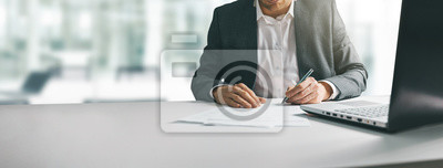 Posters young man in suit writing business papers at desk in modern coworking office. copy space