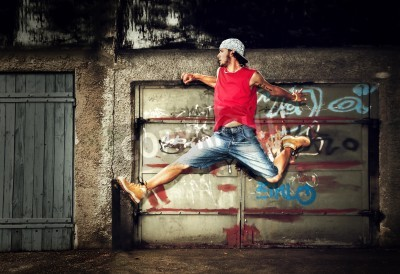 Posters Young man jumping / dancing on grunge graffiti wall background