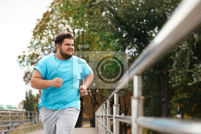 Posters Young overweight man running outdoors. Fitness lifestyle