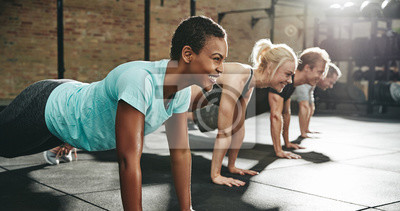 Posters Young woman smiling while doing pushups in an exercise class