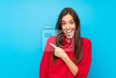 Posters Young woman with red sweater over isolated blue background pointing finger to the side
