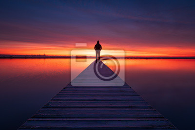 Sticker A man enjoying the colorful  dawn on a jetty in a lake. Groningen, Holland.