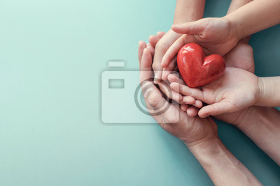 Sticker adult and child hands holding red heart on aqua background, heart health, donation, CSR concept, world heart day, world health day, family day
