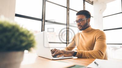 Sticker Afro man working on laptop in modern office