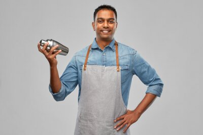 Sticker alcohol drinks, people and profession concept - indian barman in apron with cocktail shaker over grey background