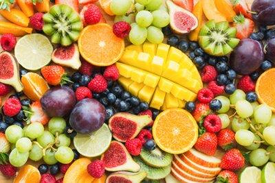 Sticker Assortiment de fond de plateau de fruits et de baies sains, fraises, framboises, oranges, prunes, pommes, raisins kiwis, myrtilles, mangue, vue de dessus, mise au point sélective
