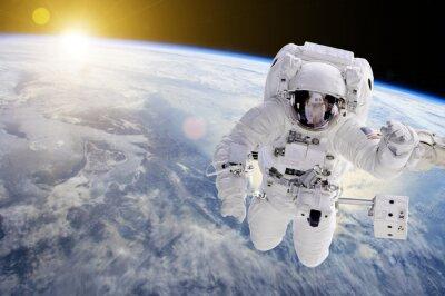 Sticker Astronaute dans l'espace, en arrière-plan notre terre et le soleil - Éléments de cette image fournis par la NASA