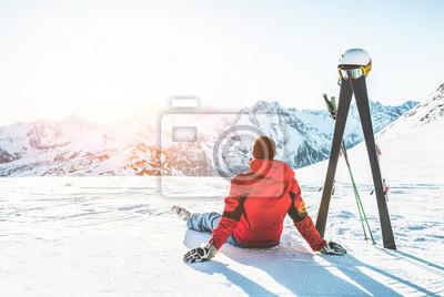 Sticker Athlète skieur assis dans les montagnes des Alpes par journée ensoleillée - Homme adulte, profitant du coucher de soleil avec le ciel engrenage à côté de lui - Sport d'hiver et concept de vacances