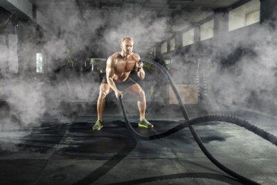 Sticker Athlétique jeune homme avec une corde de bataille, faire des exercices dans la salle de fitness. Concept sportif.