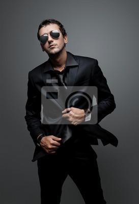 a6a7ecb919a62d Sticker attrayante jeune homme portant élégant costume noir et lunettes de  soleil