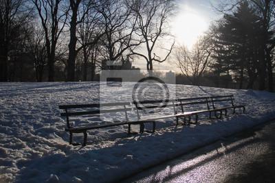 Bancs de parc sur la neige avec coucher de soleil à Central Park