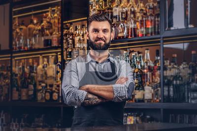Sticker Barman brutal élégant dans une chemise et un tablier debout avec les bras croisés au fond de comptoir de bar.