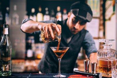 Sticker Barman créant une boisson signature au comptoir du bar. Whisey amère avec cocktail à la bière