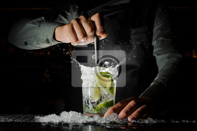 Sticker Barman main serrant le jus frais de la chaux faisant le cocktail Caipirinha