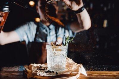 Sticker Barman prépare un cocktail à l'orange et aux herbes dans un verre transparent sur un bar avec de l'alcool. Utilise un brûleur avec des étincelles. Fond sombre.
